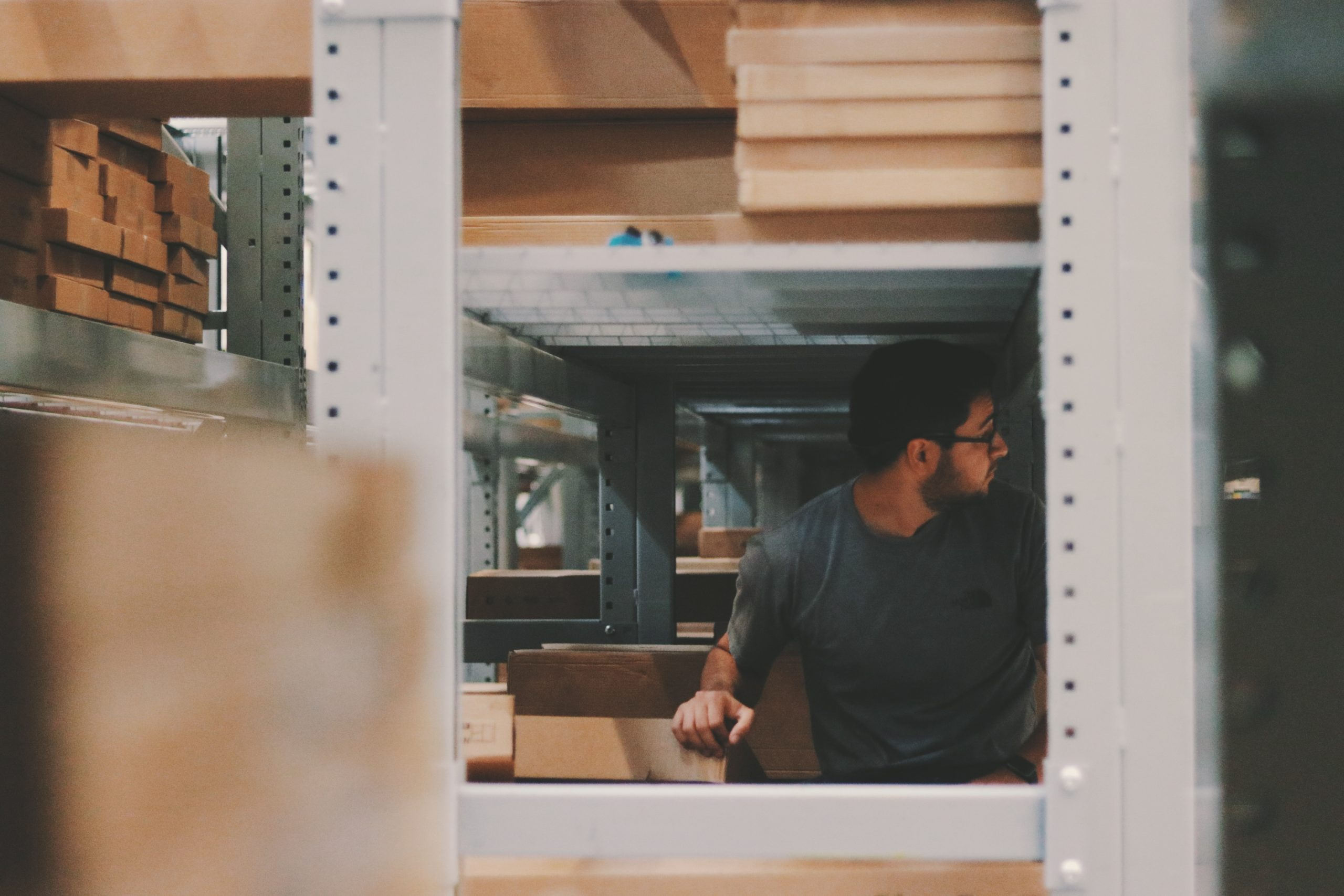man-under-a-bunch-of-large-shelves